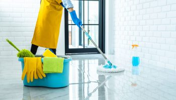 happy-young-woman-blue-rubber-using-mop-while-cleaning-floor-home